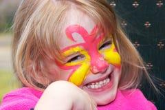 Menina de sorriso com pintura da face Fotos de Stock Royalty Free