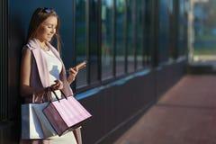 Menina de sorriso com sacos de compras e vista no telefone Foto de Stock Royalty Free