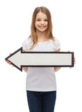 Menina de sorriso com seta vazia que aponta à esquerda Fotografia de Stock