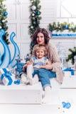 Menina de sorriso com sua irmã mais idosa que senta-se ao lado de um Chri imagens de stock royalty free