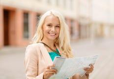 A menina de sorriso com turista traça na cidade Foto de Stock Royalty Free