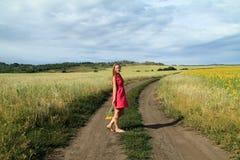 Menina de sorriso com um girassol Foto de Stock Royalty Free