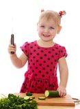 Menina de sorriso com um pepino do corte da faca Foto de Stock Royalty Free