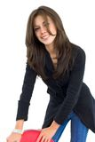 Menina de sorriso com uma cadeira vermelha Foto de Stock