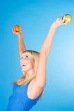 Menina de sorriso com uma maçã e uma laranja Foto de Stock