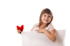 Menina de sorriso com uma placa para escrever e um coração vermelho em seu han Imagens de Stock