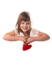 Menina de sorriso com uma placa para escrever e um coração vermelho em seu han Fotografia de Stock Royalty Free