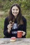 A menina de sorriso come anéis de espuma com café em uma tabela de madeira Fotos de Stock Royalty Free