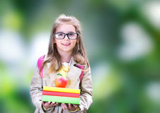 Menina de sorriso da criança com a maçã da trouxa dos livros De volta à escola Fotos de Stock Royalty Free