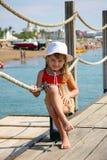 Menina de sorriso da criança que levanta como um pro modelo que senta-se em um cais Fotos de Stock