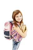Menina de sorriso da escola com os livros da terra arrendada da mochila Foto de Stock