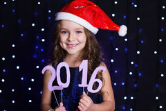A menina de sorriso de Santa com ano novo data 2016 Fotografia de Stock
