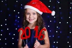 A menina de sorriso de Santa com ano novo vermelho data 2016 Imagem de Stock