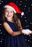 Menina de sorriso de Santa com neve falsificada nas mãos imagem de stock royalty free