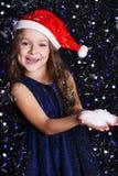 Menina de sorriso de Santa com neve falsificada nas mãos foto de stock