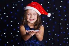 A menina de sorriso de Santa está olhando a neve nas mãos imagem de stock