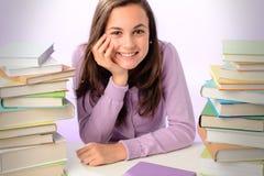 Menina de sorriso do estudante entre pilhas de livros Imagem de Stock Royalty Free