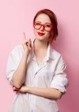 Menina de sorriso do estudante na camisa branca e em vidros vermelhos Fotos de Stock