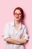 Menina de sorriso do estudante na camisa branca e em vidros vermelhos Fotografia de Stock