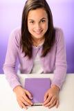 Menina de sorriso do estudante que senta-se atrás do roxo da mesa Foto de Stock
