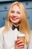 Menina de sorriso do gengibre na camisa com o laço que guarda o café Close-up foto de stock royalty free