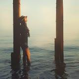 A menina de sorriso do moderno que anda em um mar encalha Imagem de Stock