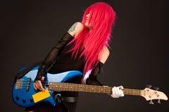 Menina de sorriso do punk com guitarra baixa Imagem de Stock Royalty Free