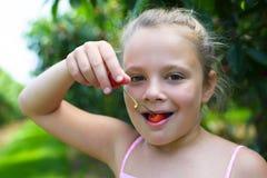Menina de sorriso do retrato do close up que come a cereja no jardim da cereja Imagens de Stock