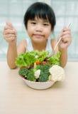 A menina de sorriso doce bonito nova pequena come a salada fresca/conceito saudável comer imagem de stock