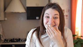 A menina de sorriso em um avental na cozinha está rasgando a massa crua com suas mãos Risos alegres da menina e enganar ao redor  vídeos de arquivo