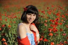 Menina de sorriso em um pano vermelho entre papoilas Fotos de Stock Royalty Free