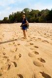 Menina de sorriso em um vestido azul que anda abaixo da areia Fotos de Stock Royalty Free
