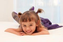 A menina de sorriso encontra-se na barriga na cama branca Foto de Stock Royalty Free