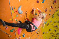 A menina de sorriso escala a parede íngreme no gym de escalada Fotos de Stock