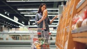 A menina de sorriso está comprando o pão fresco no supermercado que cheira o que põe então no carro com outros produtos Compra filme