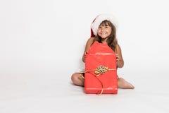 A menina de sorriso está desembalando um presente do Natal fotos de stock