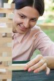 A menina de sorriso está jogando um jogo de madeira do bloco no parque Foto de Stock Royalty Free