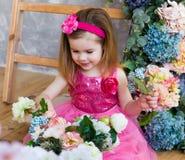 A menina de sorriso está sentando-se perto das escadas e da cor de madeira Imagens de Stock Royalty Free