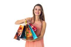 A menina de sorriso estica antes de muitos pacotes bonitos isolados no fundo branco Foto de Stock Royalty Free