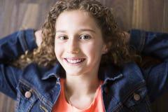 A menina de sorriso esticou em um assoalho de madeira com suas mãos atrás de sua cabeça e de olhar a câmera Foto de Stock Royalty Free