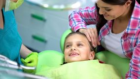 Menina de sorriso feliz após o procedimento da odontologia, dentista pediatra bem qualificado fotografia de stock