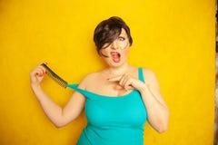 A menina de sorriso feliz bonito com cabelo preto curto com golpes tem o divertimento com um pente no fundo contínuo amarelo do e foto de stock