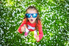Menina de sorriso feliz com cabelo encaracolado entre o campo da margarida foto de stock