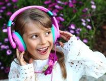 A menina de sorriso feliz com cabelo louro longo, laço veste a escuta a música em fones de ouvido em um fundo das flores da flor  Imagens de Stock