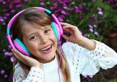 A menina de sorriso feliz com cabelo louro longo, laço veste a escuta a música em fones de ouvido em um fundo das flores da flor  Fotos de Stock Royalty Free