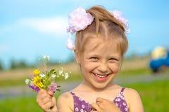 Menina de sorriso feliz com flores Imagem de Stock Royalty Free