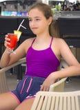 Menina de sorriso feliz com o cocktail vermelho em sua mão imagem de stock
