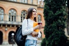 Menina de sorriso feliz do estudante com a trouxa no fundo de universidade A mulher com manuais de instruções e leva embora o caf fotos de stock
