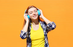 A menina de sorriso feliz escuta e aprecia a boa música nos fones de ouvido contra a laranja colorida fotografia de stock royalty free