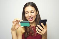 Menina de sorriso feliz que guarda o cartão esperto do telefone e de crédito em suas mãos no fundo branco Mulher do comércio elet imagens de stock royalty free